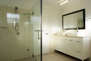 Frameless shower screen hand shower on rail double vanity on legs above counter basin