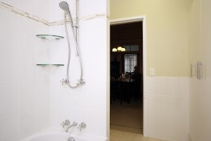 Traditional tapware hand shower on rail linen cupboard horizontal feature tile