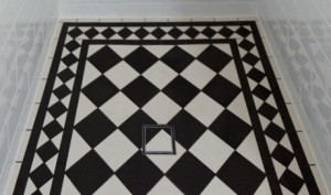 Tiles were cut by hand and individually installed to continue the geometric shower floor pattern.