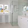 Frameless shower screen with glass shelves and hand-held shower