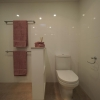 Toilet suite concealed behind wall with shelves, single towel rails