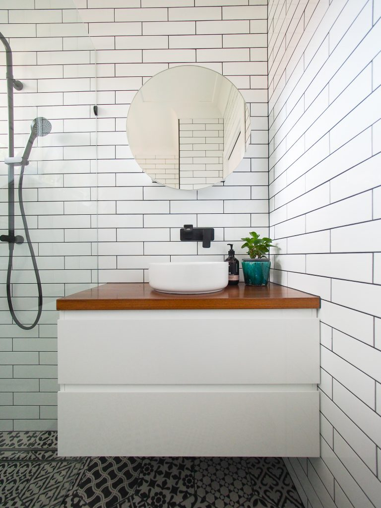 Portrait wall hung vanity timber top above mount basin white subway wall tiles patterned hexagon floor