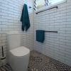 Portrait toilet suite white subway tiles black white patterned floor hexagon louvre