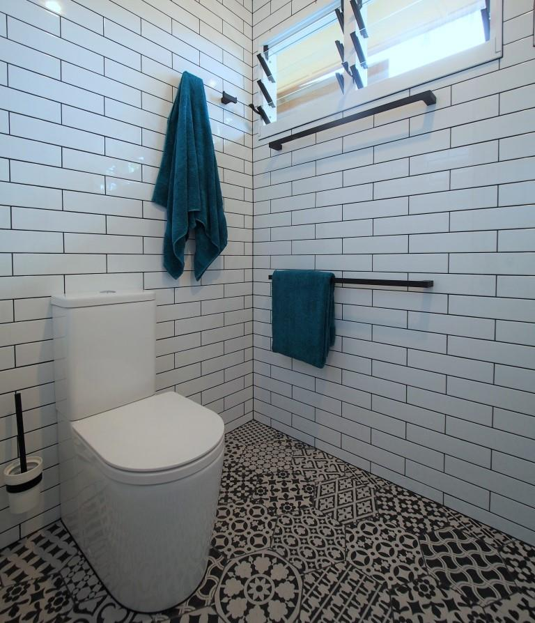 Portrait toilet suite white subway tiles black white patterned floor hexagon louvre